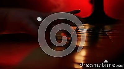Een pianist opent een deksel voor de piano en begint een rode gele achtergrond te spelen stock footage
