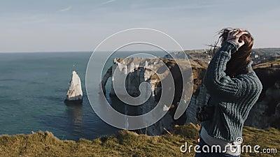 Een prachtig enthousiast vrouwelijk toerist loopt langs een prachtig Etretat-zeepanorama en rotsen met haar in de wind blazen stock footage