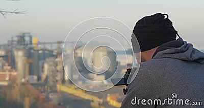 Een professionele fotograaf of videograaf verwijdert een zeehaven uit een berg met een driepoot Fotograaf met foto's stock footage