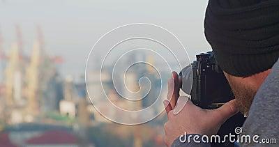 Een professionele fotograaf of videograaf verwijdert een zeehaven uit een berg met een driepoot Fotograaf met foto's stock video