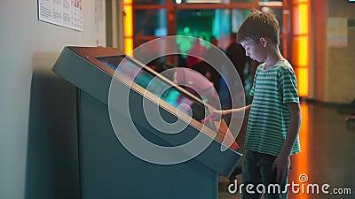 Een schooljongen staat voor een groot aanraakscherm stock videobeelden