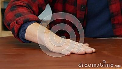 Een skinner die een groot stuk leer aanraakt op de tafel Mannelijke ledervakman onderzoekt huid voor gebreken Bepaling van stock videobeelden