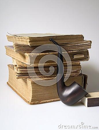 Stapel van oude boeken en een pijp