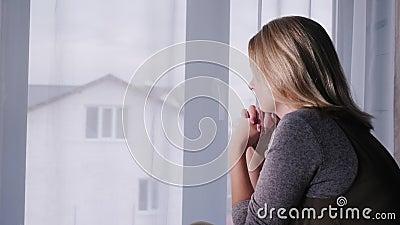 Een trieste vrouw zit nog op het raam, kijkt uit het raam naar huis stock video