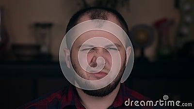 Een van de meest beledigde jonge mensen die op Europees niveau verschijnen zit in een stoel in een donkere hemd Afzetconcept stock video