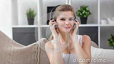Een verachtelijk positief Europees meisje met een koptelefoon die geniet van een geweldige melodie die thuis plezier heeft stock footage