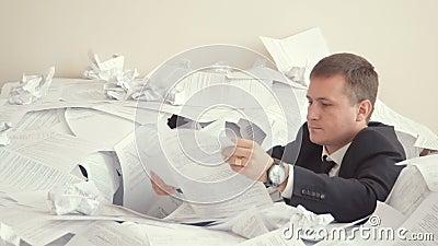 Een vermoeide werknemer zit in een stapel van documenten Problemen met het werk van de werknemer Een jonge mens in een bureaukost stock videobeelden