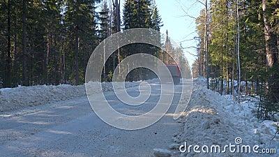 Een vrachtwagen met ertsen langs een winterbos stock video