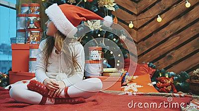 Een vrolijk meisje dat op een lotoberpositie zit en haar hoofd van zijkant naar zijkant verplaatst zodat een kerstman haar gezich stock footage