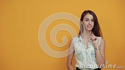 Een vrolijke brunette jonge vrouw wint, ziet er mooi uit, hij houdt de vinger op de wang stock footage