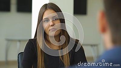 Een vrouw beantwoordt vragen van de werkgever bij het gesprek stock footage