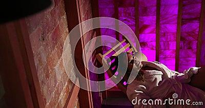 Een Vrouw legt op een Houten Lanterfanter in een Zoute Sauna bij een Duur Hotel Roze muur Therapeutische Sauna, Therapie, Geneesk stock video
