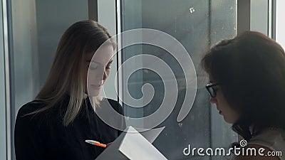 Een vrouw leidt een vragenlijst van een baankandidaat voor een baan stock footage
