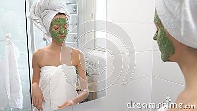 Een vrouw met een groen bevochtigend masker op haar gezicht ziet zich plotseling in de spiegel en bang gemaakt stock footage