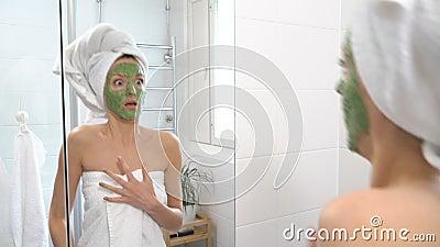 Een vrouw met een groen bevochtigend masker op haar gezicht ziet zich plotseling in de spiegel en bang gemaakt stock videobeelden