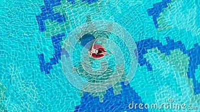 Een vrouw rusten op een rubberen ring in een groot zwembad stock video