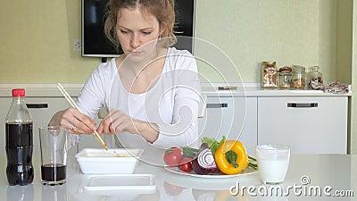 Een vrouw zit bij een lijst etend Chinese noedels en verse groenten stock videobeelden