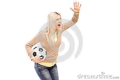 Een vrouwelijke sportventilator die een voetbal en het schreeuwen houden