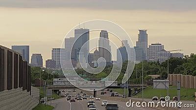 Een was van oranje middaglicht over de ver horizon van Minneapolis en wegverkeer in de voorgrond stock videobeelden
