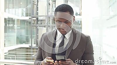Een zwarte mens gebruikt zijn telefoon voor zaken Het Afrikaans Amerikaans bedrijfs professioneel werk aangaande zijn mobiele tel stock footage