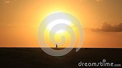 Eenzame mens op zandig strand onder grote zon stock video