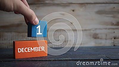 Eerste dag van december van maand, de hand zet de dag van de maand op de naam van de maand op een houten achtergrond winter, dag stock footage