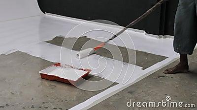 Eerste keer van arbeider die en epoxyhars op concrete vloer schilderen met een laag bedekken stock videobeelden