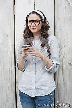 Eftertänksam moderiktig kvinna med stilfulla exponeringsglas som överför textmeddelandet