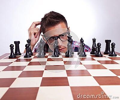 Eftertänksam man framme av hans första schackflyttning