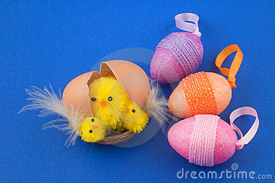 Egg with easter chicks and colorful eggs