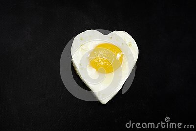 Heart-shaped grilled egg on a black background. An egg, fried sunny side up and heart-shaped, on black background. Keto and paleo friendly breakfast royalty free stock photo