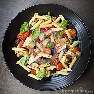 Eggplant, chilli and tomato penne pasta, on a black serving platter ...