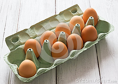 Eggs in egg-box on white wood background