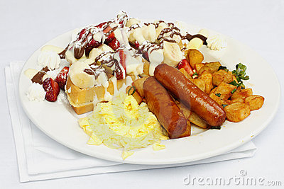 Eggs sausage potatos and waffle with fruit