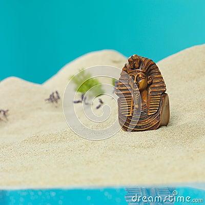 Egyptian bust in miniature sandy landscape