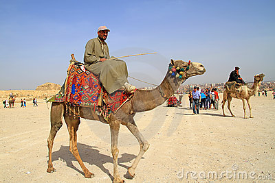 Egyptian guide offering to tourists camel ride Editorial Photography