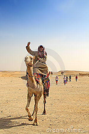 Egyptian guide offering to tourists camel ride Editorial Stock Image