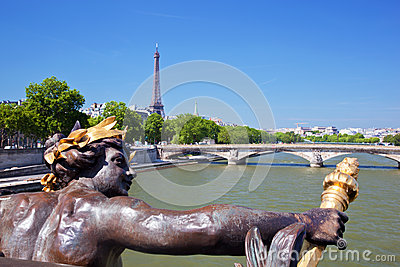 Eiffel Tower, artistic statue and bridge on Seine river in Paris, France.