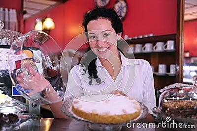 Eigenaar van een koffie die een cake toont