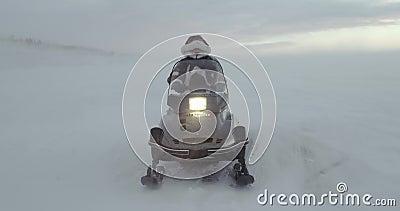 Ein Abenteurer kleidete im Renmantel mit Pelzhaubenblicken weg auf einem Schneemobil fahrung am Blizzard an Arktische Expedition  stock video