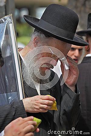 Ein alter orthodoxer Jude im schwarzen Hut wählt Zitrusfrucht aus Redaktionelles Stockfotografie