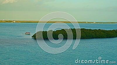 Ein Boot verankert durch eine kleine Insel bei Sonnenaufgang stock footage