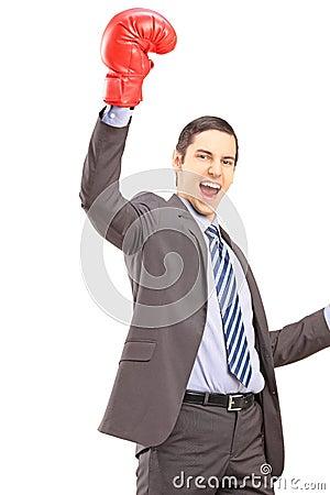 Ein glücklicher junger Geschäftsmann mit roten Boxhandschuhen happi gestikulierend