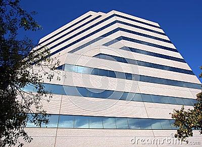 Ein hohes Bürohaus reflektiert Wolken