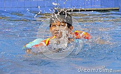 Asiatischer indischer Junge übendes Schwimmen in seinem Sommerlager
