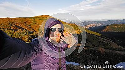 Ein junger Blogger mit einer Videokamera, der über soziale Netzwerke von oben in den Bergen aufzeichnet oder strebt, windet sich  stock footage