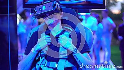 Ein junger blonder Mann sitzt auf dem Testen des Helms der virtuellen Realität vr oculus Technologie Realität Smartphone elektron stock footage