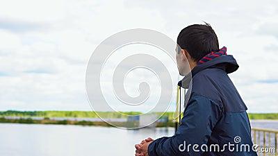 Ein junger Mann steht auf einer Brücke und untersucht den Abstand stock video footage