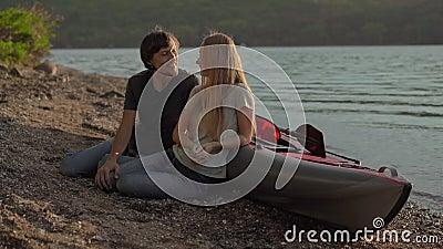 Ein junger Mann und eine junge Frau, die an einem großen aufblasbaren Kajak am Meer oder am See sitzt stock video