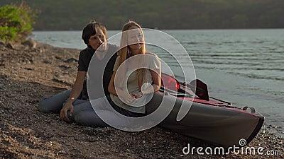 Ein junger Mann und eine junge Frau, die an einem großen aufblasbaren Kajak am Meer oder am See sitzt stock video footage